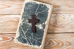 Wooden Christian cross on bible. Stock Photos