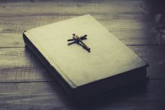 Wooden Christian cross on the Bible. A wooden cross tied with a thread on the closed Holy Bible. A black book on a wooden surface. The way to God through prayer royalty free stock images