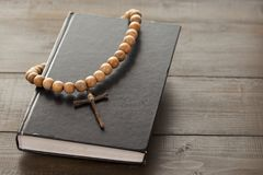 Wooden Christian Cross on the Closed Bible. A wooden cross with a rosary on a closed Holy Bible. The way to God through prayer. Closed book with a black cover stock images