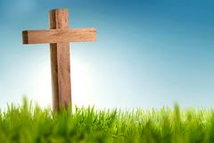 Wooden christian cross on green grass. With blue sky background Royalty Free Stock Image