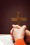 Wooden Christian cross hand next on holy Bible Royalty Free Stock Image