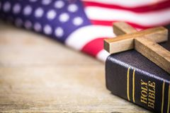 Christian Cross and Bible American Concept. A wooden Christian cross laying on a holy Bible with an American flag background stock image