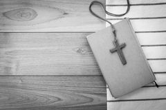 Wooden Christian cross necklace on holy Bible on wood table Stock Image