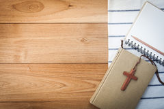 Wooden Christian cross necklace on holy Bible on wood table Royalty Free Stock Images