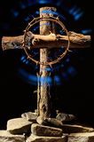 Christian cross, crucifix with a radiating crown of thorns; Resurrection of God, Jesus. Wooden Christian cross with a radiating crown of thorns. Stands on stones Royalty Free Stock Photos