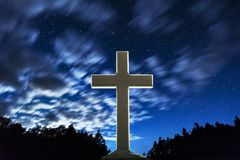 Wooden Christian cross standing under a fast moving cloud sky at. Night, backlit by white. Symbol of Jesus and worship background Stock Image