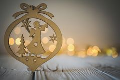 Wooden Christmas angel ornament against a blurred background of fairy lights. Wooden Christmas angel ornament on a white wooden table against a blurred stock images