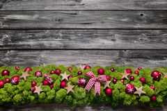 Wooden christmas background with green moos and red balls. Royalty Free Stock Photography