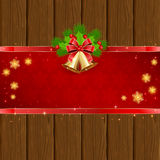 Wooden Christmas background with red bow and bells Stock Photos