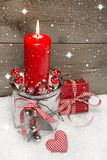 Wooden Christmas background with a red candle and a gift box on Royalty Free Stock Images