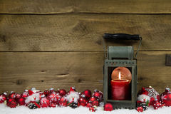 Wooden christmas background with red candle in a latern and snow Stock Photo