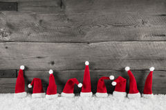 Wooden christmas background with red santa hats for a festive fr. Ame Stock Images