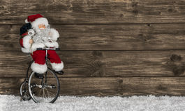 Wooden christmas background with santa on a bike. Funny greeting Royalty Free Stock Photos