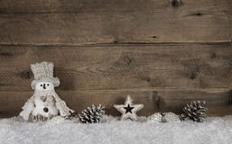 Wooden christmas background with a snowman and natural decoratio Stock Photos