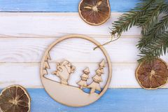 Wooden Christmas ball and decorations. Dried lemons, ball and a branch of a tree. Santa in a ball on a bright background royalty free stock photo