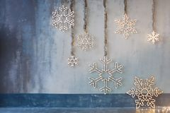 Wooden christmas decoration for the walls. Glowing snowflakes with garland lights on gray concrete background. Christmas. Background, winter holidays theme stock photography