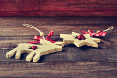 Wooden christmas ornaments on a rustic wooden surface. Some wooden christmas ornaments, such as a reindeer and a star, on a rustic wooden surface Royalty Free Stock Photos