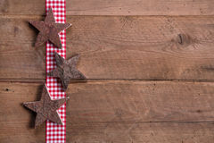 Wooden Christmas stars on checkered ribbon on wooden background Stock Photography