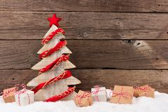 Wooden Christmas tree with rustic red garland in snow Stock Image