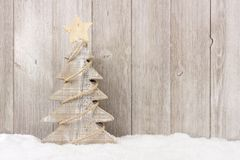 Wooden Christmas tree with twine garland in snow Stock Photo
