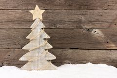 Wooden Christmas tree with twine garland in snow Royalty Free Stock Photos