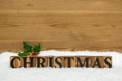 Wooden Christmas Word with holly and snow Royalty Free Stock Images