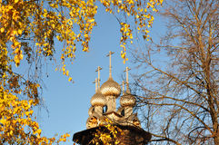 Wooden church. Wooden dome of the church among the birch twigs in the fall stock photography