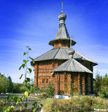 Wooden church in the Far East. Against the backdrop of autumn forest and blue sky Royalty Free Stock Image