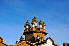 Wooden Church with Golden domes was consecrated by the sun against a blue sky background. Russia, Belgorod. Landscape orientation Royalty Free Stock Photos