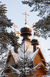 Wooden church and the golden domes of the winter forest Stock Images