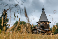 Wooden church in the oat field Malye Korely. Ancient russian wooden church in the oat field Stock Photography