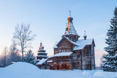 Wooden church in snowy winter forest at sunset Stock Images