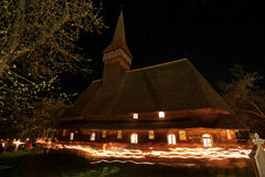 Wooden church surrounded by people with lit candle. Wooden church in Hoteni, Maramures, Romania surrounded by people with lit candles, Easter traditions Stock Photos