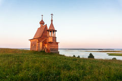 Wooden church on the top of the hill. Vershinino village sunset view. Arkhangelsk region, Northern Russia. Wooden church on the top of the hill. Vershinino Stock Image