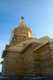 Wooden church under construction. On the blue sky background with doves Royalty Free Stock Photos