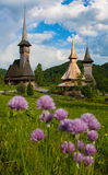 Wooden Churches of Maramures. Three churches made from wood in Maramures, Romania. They are the traditional churches in that area. Several flowers are in the stock images