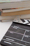 Wooden clapper board with a pile of books. Black wooden clapper board with a pile of books Stock Images