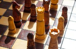 Wooden classic chessboard. White queen in center of attention. Strategy concept stock images