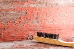 Wooden cleaning brush against red ragged wall. Wooden cleaning brush against red ragged painted wall with copy space stock photo
