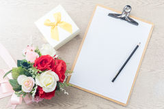 Wooden Clipboard attach planning paper with pencil beside rose b Stock Images