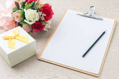Wooden Clipboard attach planning paper with pencil beside rose b Royalty Free Stock Photography