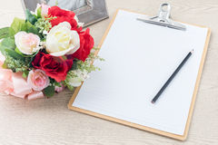 Wooden Clipboard attach planning paper with pencil beside rose b Royalty Free Stock Photo