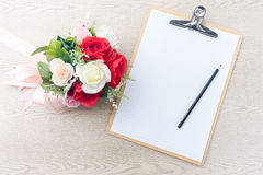 Wooden Clipboard attach planning paper with pencil beside rose b Royalty Free Stock Images