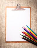 Wooden clipboard and colored pencils on old sackcloth background Stock Photography
