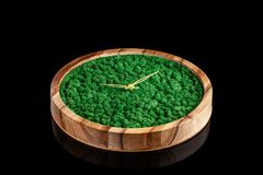 Wooden clock with color stabilized moss on a black background with mirror otgruzheniya. Trend 2019. Wall Clock copy space stock photo