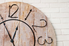 Wooden clockface on white wall Stock Photo