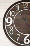 Wooden clockface on white wall stock photos
