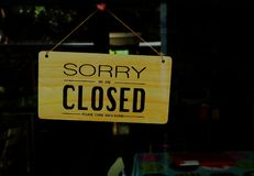 Sorry we are closed. A wooden closed sign hanging on window of a shop with words read sorry we are closed, please come back again stock images