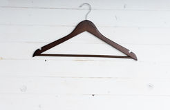 Wooden clothes hanger. On white wooden background Stock Photos