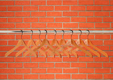 Wooden clothes hangers over orange brick wall Royalty Free Stock Image